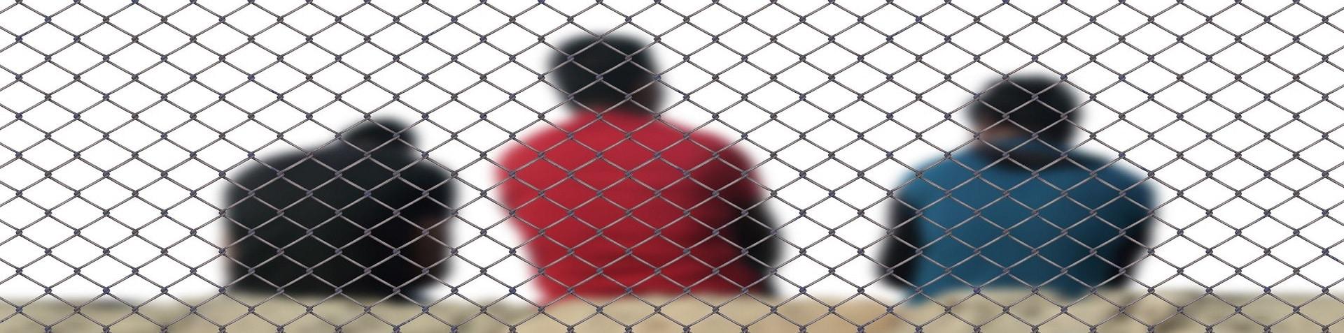 Rechtsanwalt Abschiebung: Personen sitzen hinter einem Zaun